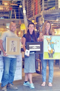 "Community Skis co-owners Michael Lish and Kristin Broumas flank artist Laurel Stanford-Manning (center), displaying images of ""beasties."" Photo courtesy: Evans."